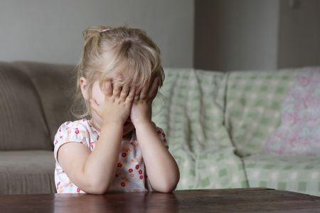 ashamed: Un ni�o peque�o ocultar su rostro detr�s de sus manos, podr�a ser asustado, jugando, recuento, t�mida o avergonzado  Foto de archivo