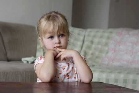 Horizontal photo of a 3 year old blond girl watching TV
