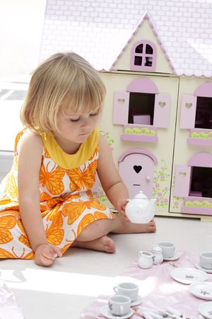 A little 4 year old girl playing with her teapot set infront of a wooden dollhouse Stock Photo