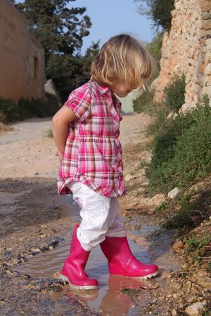 Girl with boots jumping in puddle Banque d'images - 7632562