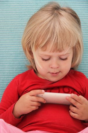 Little girl watching a film on a touchphone Stock Photo - 7632564