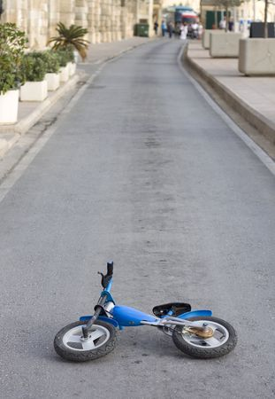 An old kids push bike is abandoned in the middle of the road. A crowd looking at the far distance photo