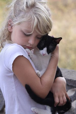 A young girl is sweetly hugging her black and white cat. Both have their eyes closed.