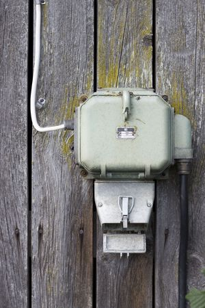 An old electricity supply box hanging on a wooden barn wall photo