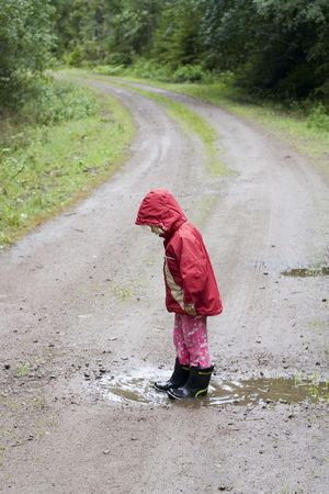 A little 4 year old girl is standing in a rain pu ddle on a country road in the rain Stock Photo