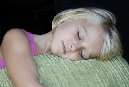 A beautiful blond girl is sleeping on a green cordiroy pillow. Isolated on black Stock Photo