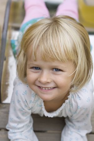 Portrait of a blond beautiful little 4 year old girl coming down the slide. Positive feeling. Stock Photo - 8001466