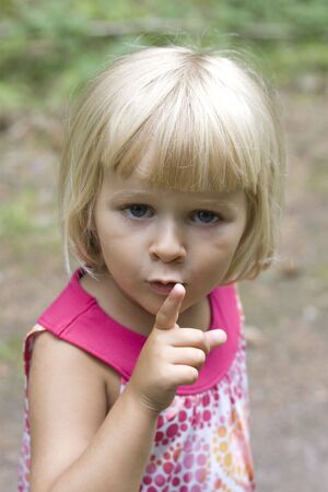 3 year old: A 3 year old little girl holding up her finger for silence