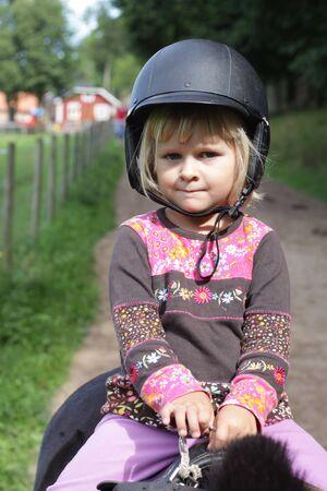 riding helmet: Close up, de unos 4 a�os de edad, ni�a sentada sobre un caballo con un casco de conducci�n
