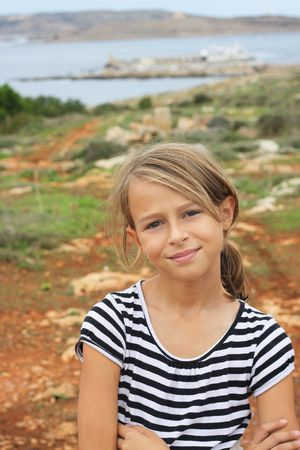 Malta: A beautiful ten year old girl smiling to the camera, with a beautiful view behind her