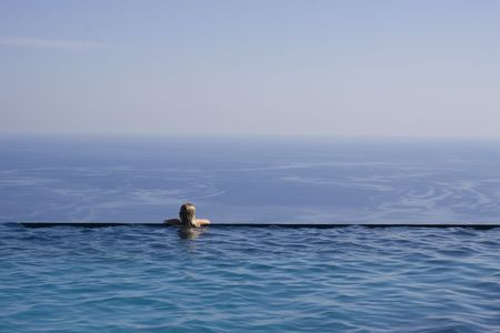 A girl resting at the end of a stunning infinity pool. Space for text photo