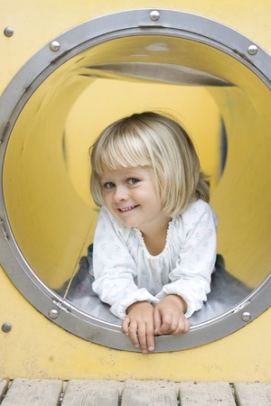 A cute little girl peeking out from a play ground tunnel, smiling at the camera.  Stock Photo