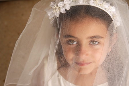 A young girl in her holy communion outfit looking at the camera from behind her veil. Stunning green eyes photo