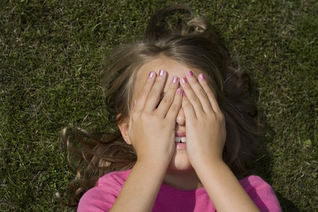 A teenage girl lying in the grass, hiding her face behind her hands photo