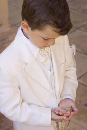 prima comunione: Bambino tenendo un Rosario con un crocifisso durante la sua prima celebrazione di comunione