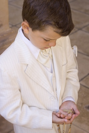 Child holding a rosary with a crucifix during his first communion celebration Stock Photo - 9976810