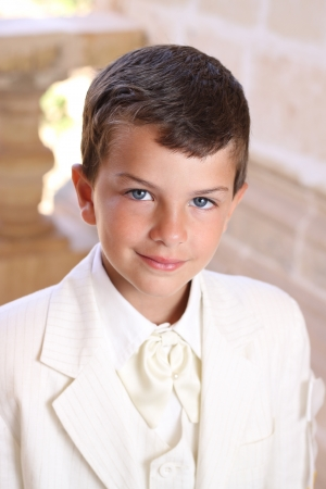 Portrait of boy doing his holy communion dressed in white wedding suite jacket photo
