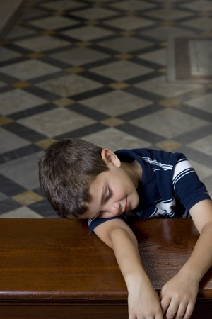 sleeping at desk: A small boy sleeps over a church pulpit