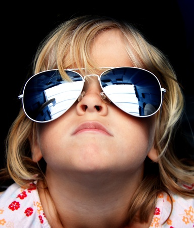 Close up of a young child wearing funky reflective sunglasses