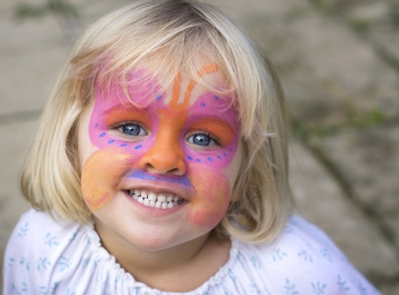 A 4 year old girl smiling at the camera with a butterfly painted over her face Stock Photo