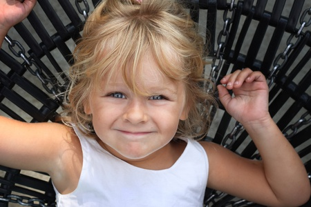 Little girl lying on a large swing, looking at the camera. photo