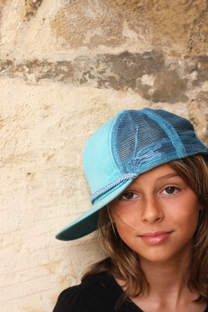 baseball caps: A pretty teenage girl smiling towards the camera with her back against a stone wall. With attitude but still friendly. Having a blue baseball cap on