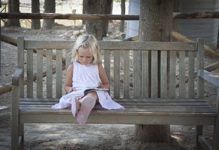 A little girl sitting on a park bench in Italy, reading a book