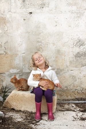 A little preschool child holding a cat, with her eyes closed, sitting against a wall on a farm Stock Photo