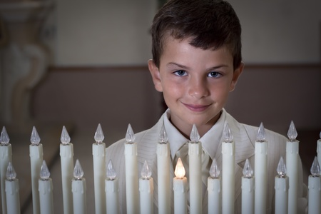 Boy in church behind a row a church candles. Slight vignette, blurred background