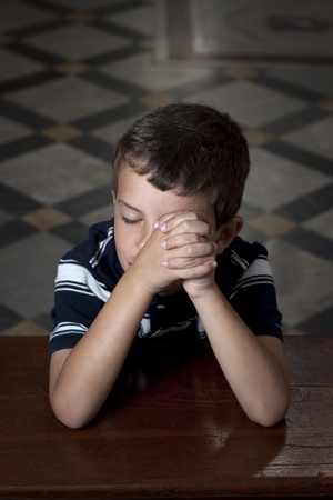 A young boy praying in church with eyes closed photo