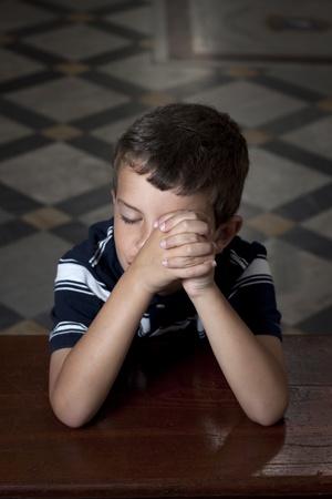 personas orando: Un niño rezando en la iglesia con los ojos cerrados