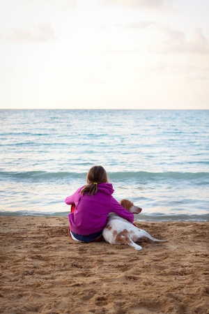 A young female looking out at sea, cuddling her pet dog. Slight vignette Stock Photo