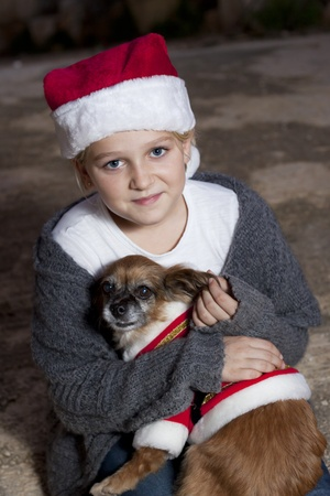 Girl dressed in christmas hat holding a dog with christmas costume photo
