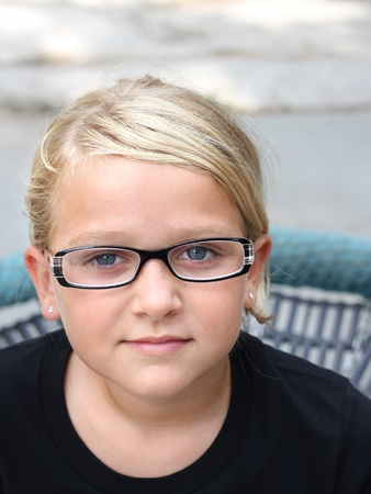 Beautiful, serious child looking at the camera, wearing glasses Stock Photo - 12193690