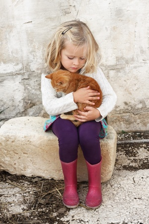 A young child hugging a small kitten, very tender moment, lots of love Stock Photo