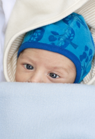 squinting: Close up of infant with a cute little blue hat, squinting, crosseyed, funny face Stock Photo