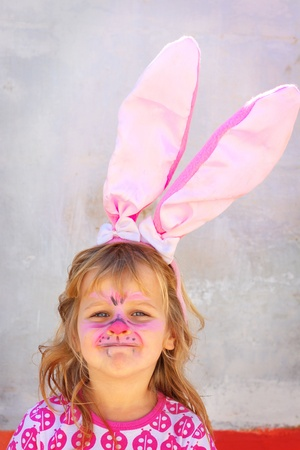 Girl dressed up as an easter rabbit with rabbit ears and facepaint  Smiling at the camera, happy feeling  Space for text Stock Photo - 17035489