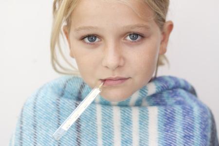 ojos tristes: Primer plano de un niño con fiebre termómetro, envuelto en una manta Foto de archivo