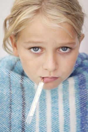 Child with a fever thermometer in her mouth, looking sad and sick