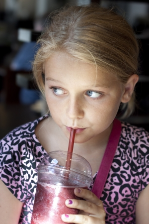 Child having a fresh shake, vertical portrait photo