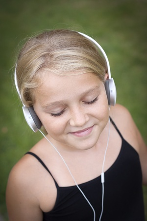 smiling child with headset listening to music photo