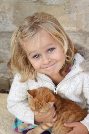 feeling positive: Litte lindo muchacha que sostiene un gato sentimiento positivo Foto de archivo