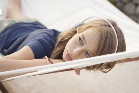 daydream: A beautiful young girl with headset day dreaming in a hammock  Golden light Stock Photo