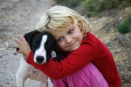 A young girl hugging a puppy