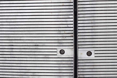 Close up of panels with horizontal slats cladding a facade with rusty screws photo