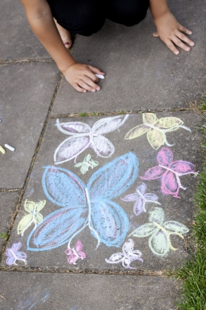 Pavement with a butterfly chalkdrawing and hands of a child