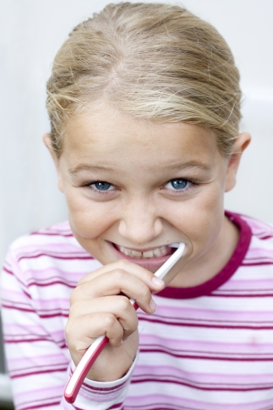 Portrait of young girl brushing teeth, isolated on white Stock Photo - 17261040