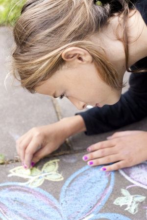 Child drawing with chalk on sidewalk photo