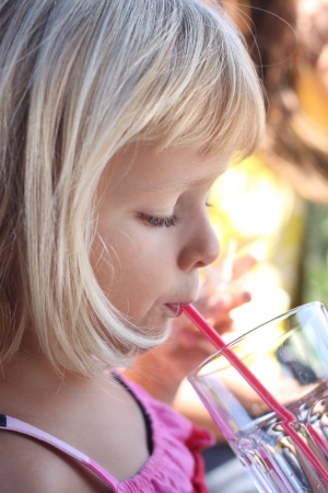 Profile portrait of young child drinking with a straw photo