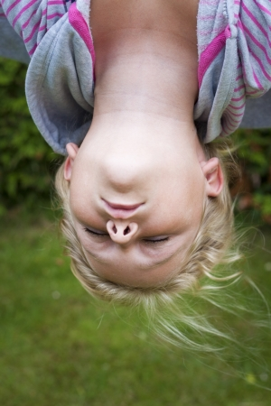 A girl haning upside down with eyes closed.  photo
